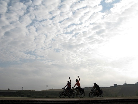 Cyclists wave in the early morning light