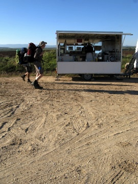 Pilgrims pass the coffee van