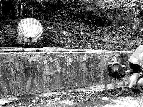 A cyclist leaves the fountain before Saint Xil