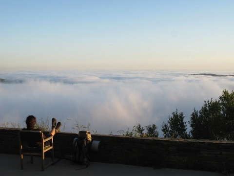 A pilgrim contemplates the descent into the cloud below O Cebreiro