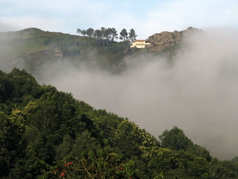 The cloud lifts to reveal a house perched on the hill