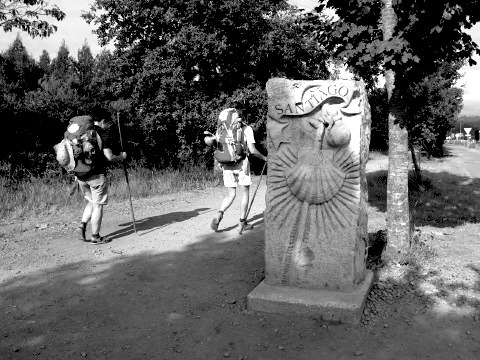 Two walkers pass the entrance to Santiago de Compostela