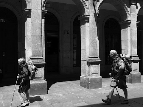 Two walkers pass through the streets of Santiago de Compostela